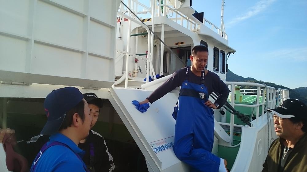 帰港後、次の漁に向けて前船長(右端)と相談